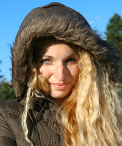 Lady with wavy blonde hair wearing a jacket with the hood on