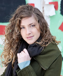 Lady with curly hair wearing a jacket and clutching her scarf