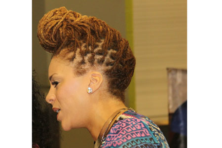 Lady with loc'd hair styled in an updo