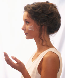 lady with lotion on her face wearing a curly bun