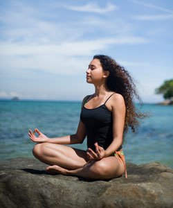 Lady with curly hair meditating on the beach