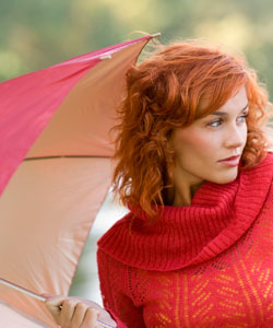 lady with red wavy hair wearing a red sweater holding a red umbrella