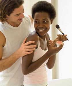 couple smiling, lady with coily hair applying makeup