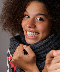 young lady with coily hair smiling and bundled in a scarf