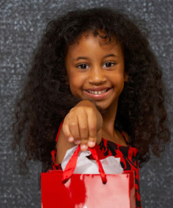Curly girl holding a gift bag