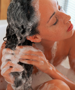 Curly haired woman shampooing hair
