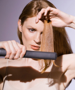 Woman straightening her hair with a flat iron