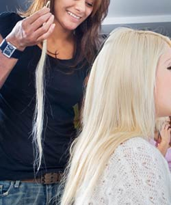 Woman receiving hair extensions at a salon