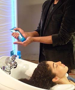 Stylist applying L'Oreal EverCurl Hydracharge