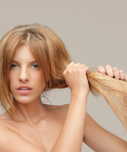 Woman holding heat damaged hair