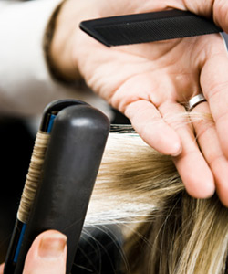 Hairstylist straightening woman's hair