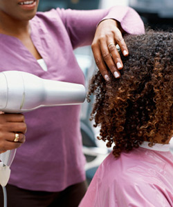 Stylist blow drying curly hair