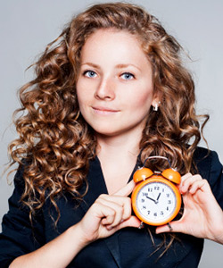 Curly haired woman holding clock