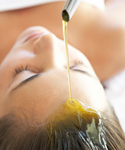 Woman pouring olive oil on hair