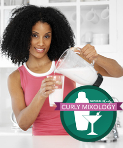 Curly haired woman with a blender