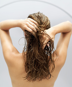 Wavy haired woman with fingers in wet hair