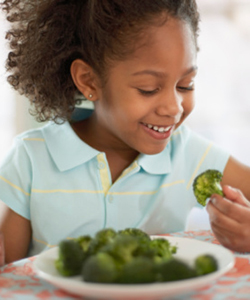 Curly haired child eating broccoli