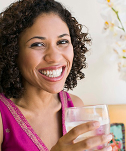 Curly haired woman drinking glass of water