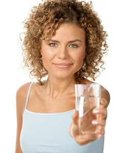 Curly haired woman holding glass of water