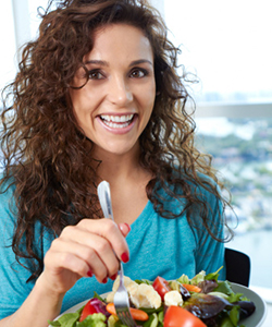 Curly haired woman eating a healthy meal