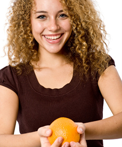 Curly haired woman holding orange