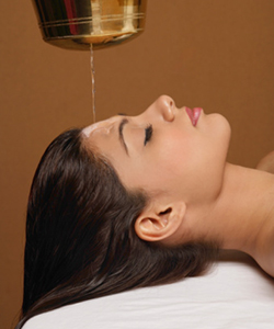 Woman receiving oil hair treatment