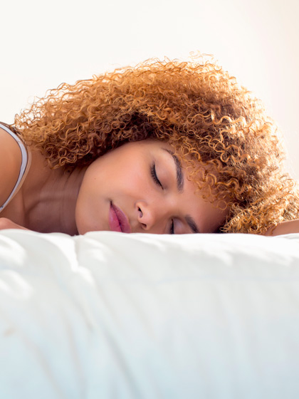 Curly haired woman sleeping on silk pillowcase