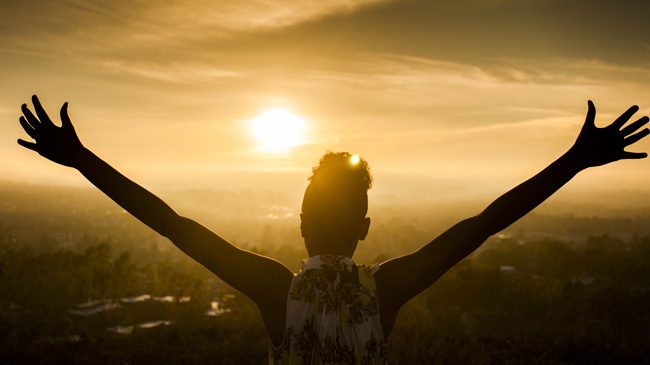 A black woman holds her arms out to the sun