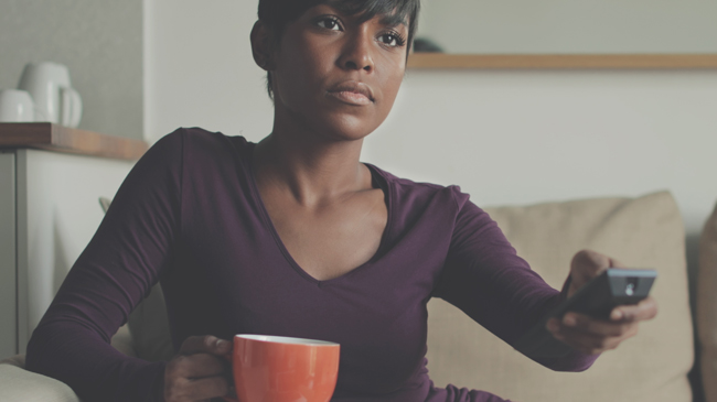 A woman points her remote with a blank expression