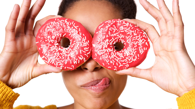 A black woman holds donuts up to her eyes with a silly expression